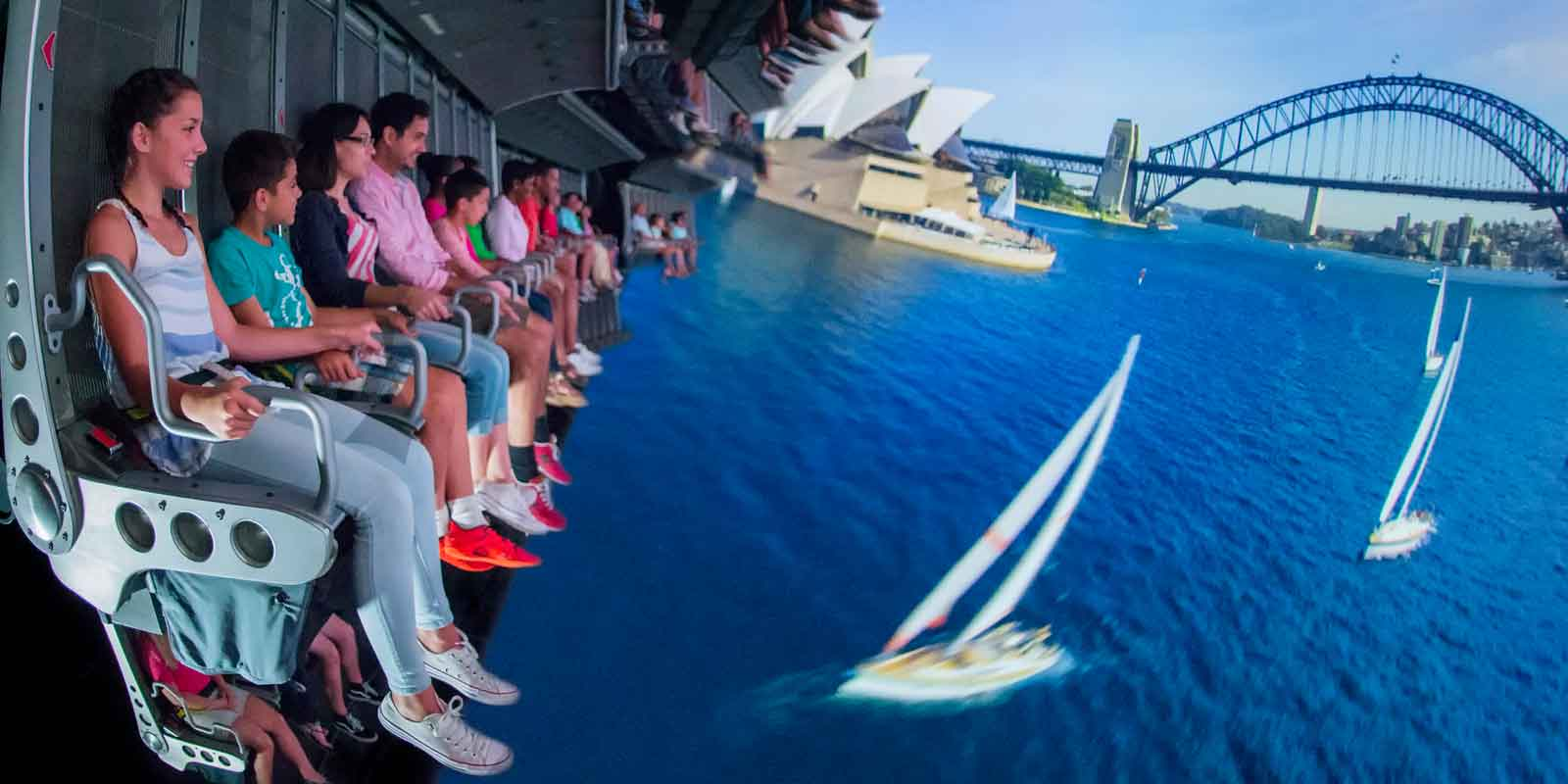 A group of people suspended in air in front of a massive virtual reality screen for the Epcot ride, Soarin.
