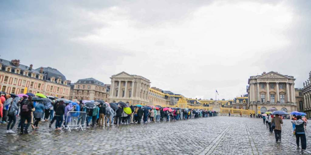 Photograph of a large crowd of people lining up outside the Palace of Versailles in France.