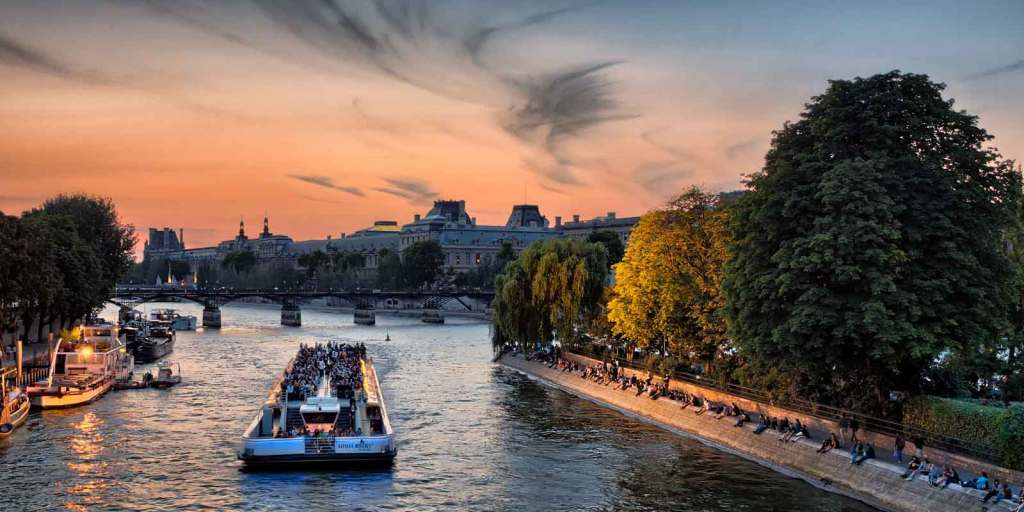 A Seine River cruise boat with passengers floats along the Seine River at sunset.