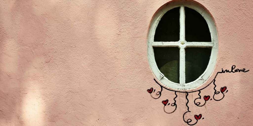 """Close up photograph of a peach wall with a single oval window. Underneath the window is a small piece of art featuring hearts, squiggly lines, and text that reads, """"in love."""""""