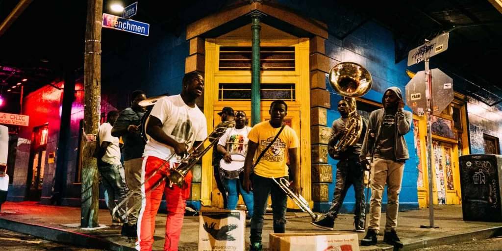 A group of young people perform music with brass instruments on a corner of Frenchman Street in New Orleans, a section well known for Jazz clubs.