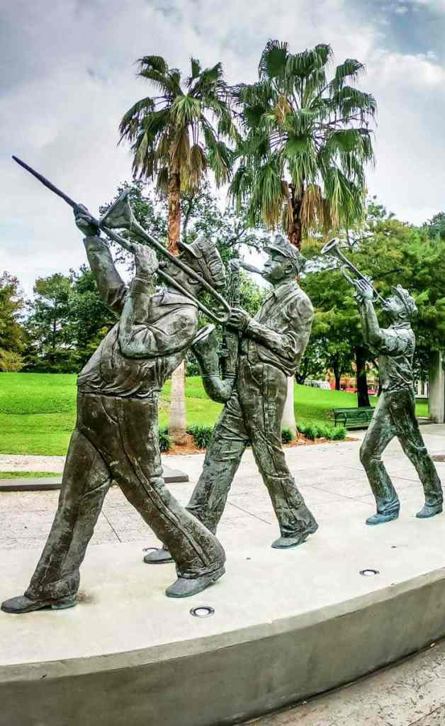 Photo of a statue featuring 3 men playing brass instruments in New Orleans' Louis Armstrong Park