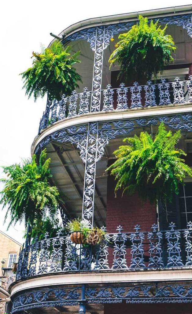 Closeup of a hotel in New Orleans' French Quarter with 3 floors of balconies featuring iron rails and hanging plants.