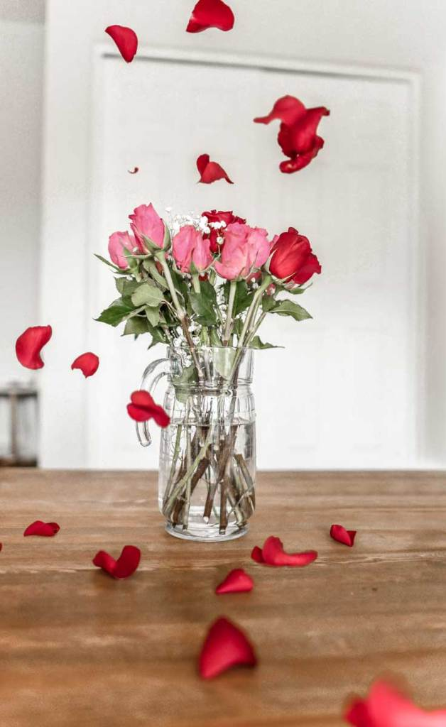 Vase of pink and red roses with red rose petals floating down like rain.