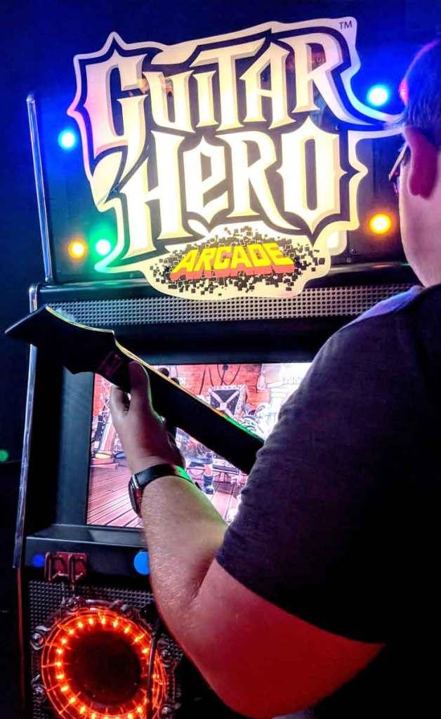 Closeup of a man playing Guitar Hero at an arcade.