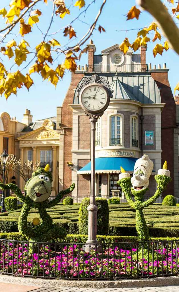 Photo of 2 topiaries, 1 shaped like Cogsworth and 1 shaped like Lumiere, characters from Beauty & the Beast.
