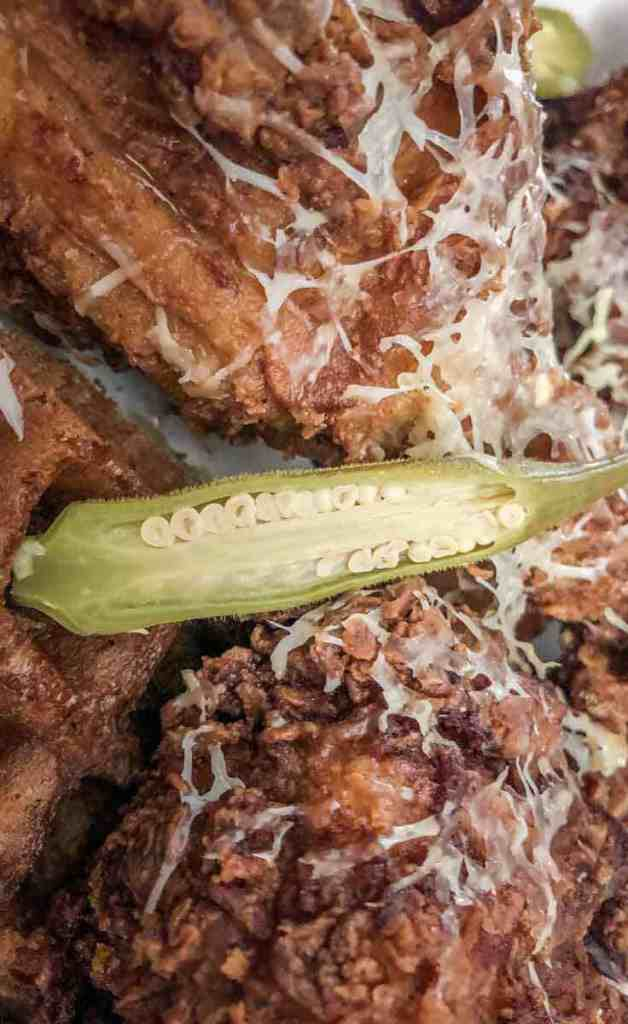 Closeup shot of fried chicken covered in shredded cheese and okra, on top of waffles.