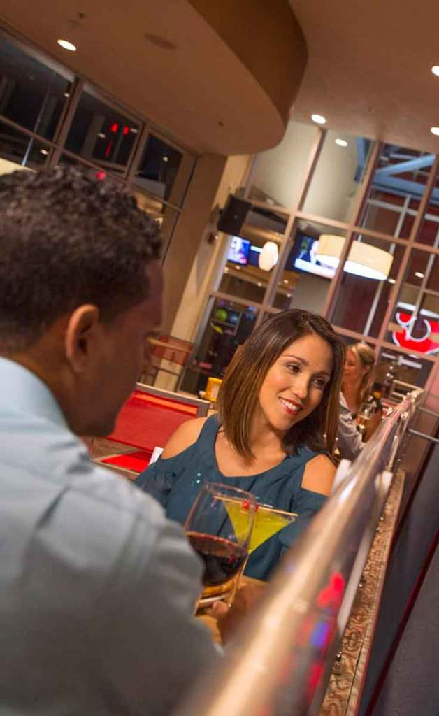 A couple enjoys a glass of wine and a cocktail on the outdoor patio at Splitsville Disney Springs.