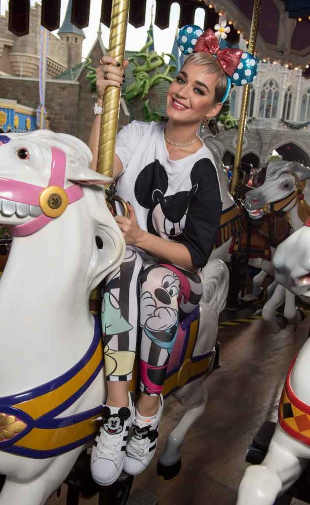 Photo of Katy Perry sitting on a carousel horse at Disney World.