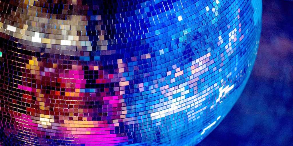 Close up view of a disco ball with blue and bright pink reflecting in the ball.