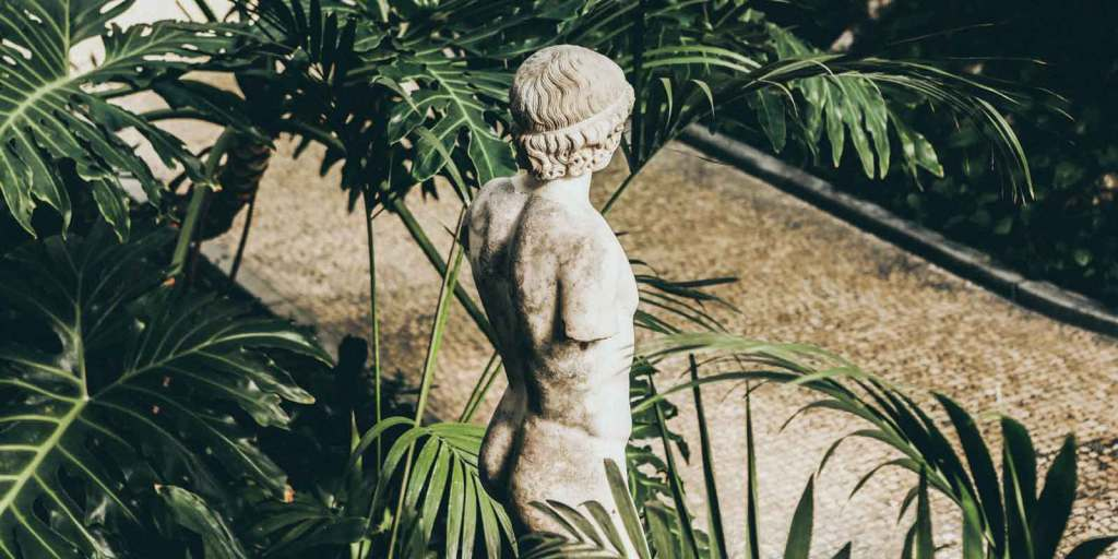 Armless statue amidst large leaves and plants with a tan stone sidewalk nearby.