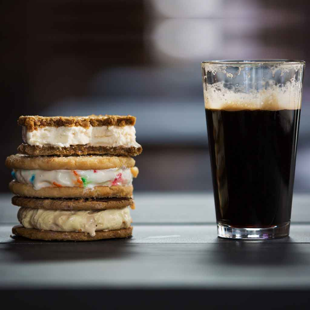 A stack of 3 ice cream cookie sandwiches sits next to a pint of dark beer.
