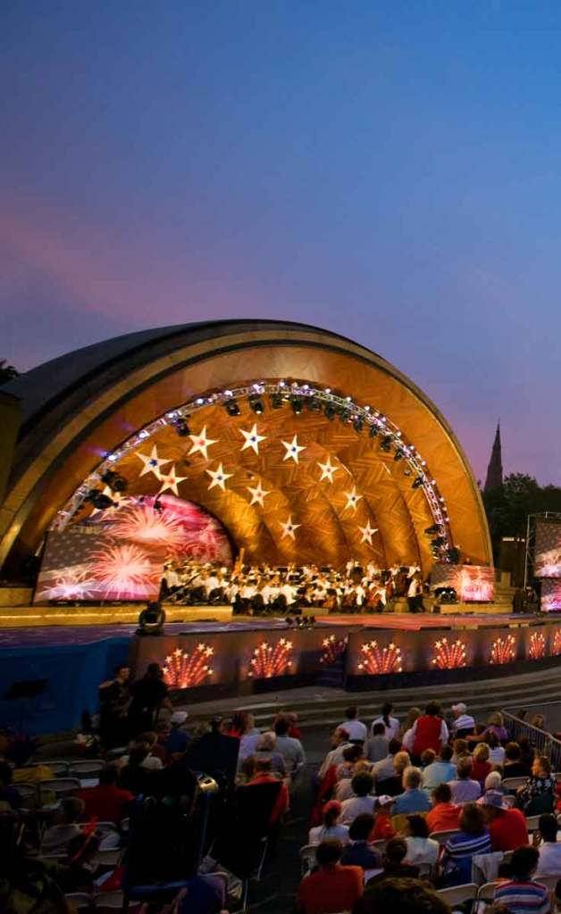 Boston Pops Orchestra performing on July 4th in the Hatch Shell stage along the Charles River in Boston at dusk.