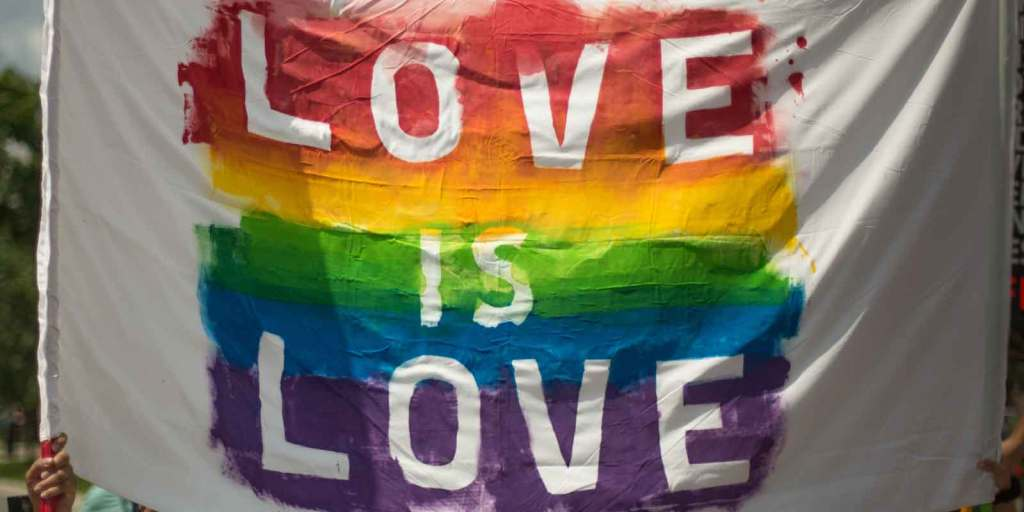 """Close up of a sign that says """"Love is Love"""" with rainbow colored stripes behind white letters."""