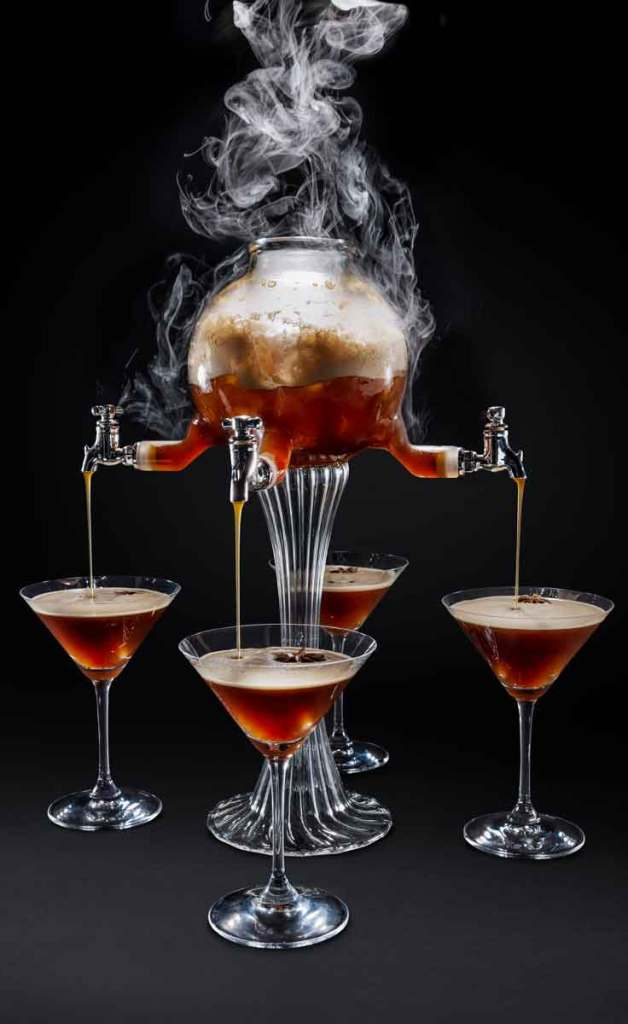 Photograph of a steaming and bubbling drink dispenser with 4 spouts, all pouring an espresso cocktail into martini glasses.