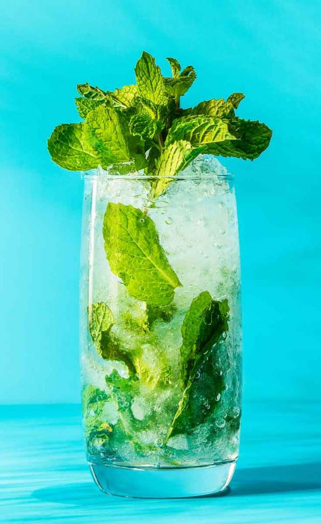Closeup of a classic mojito cocktail with lots of mint leaves, set against a bright turquoise background.