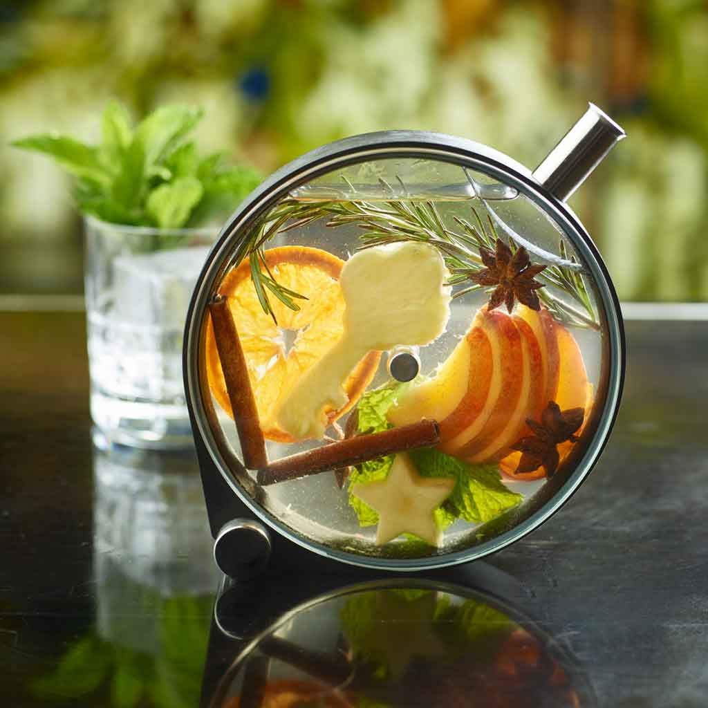 Closeup of a cocktail in a round, cask-link container. Inside are cinnamon sticks, a sprig of rosemary, orange slices, apple slices, and other garnishes.