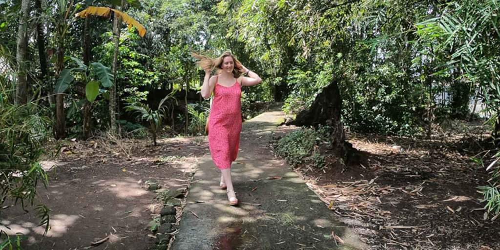 A woman flipping her hair while walking down a cement path in a tropical setting