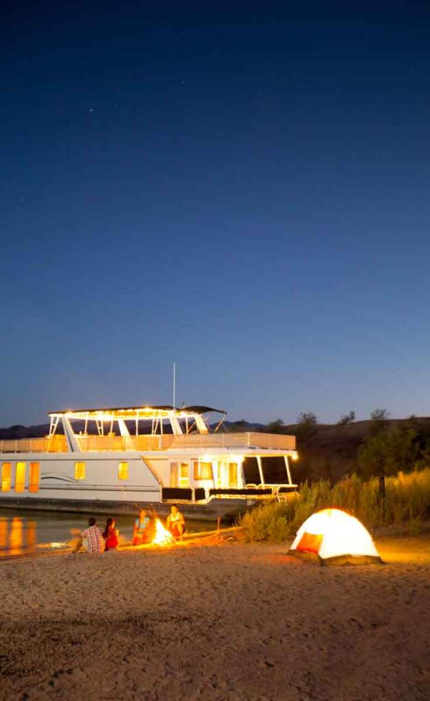 A boat docked along Lake Havasu at night with people sitting around a bonfire and a tent on the shore.