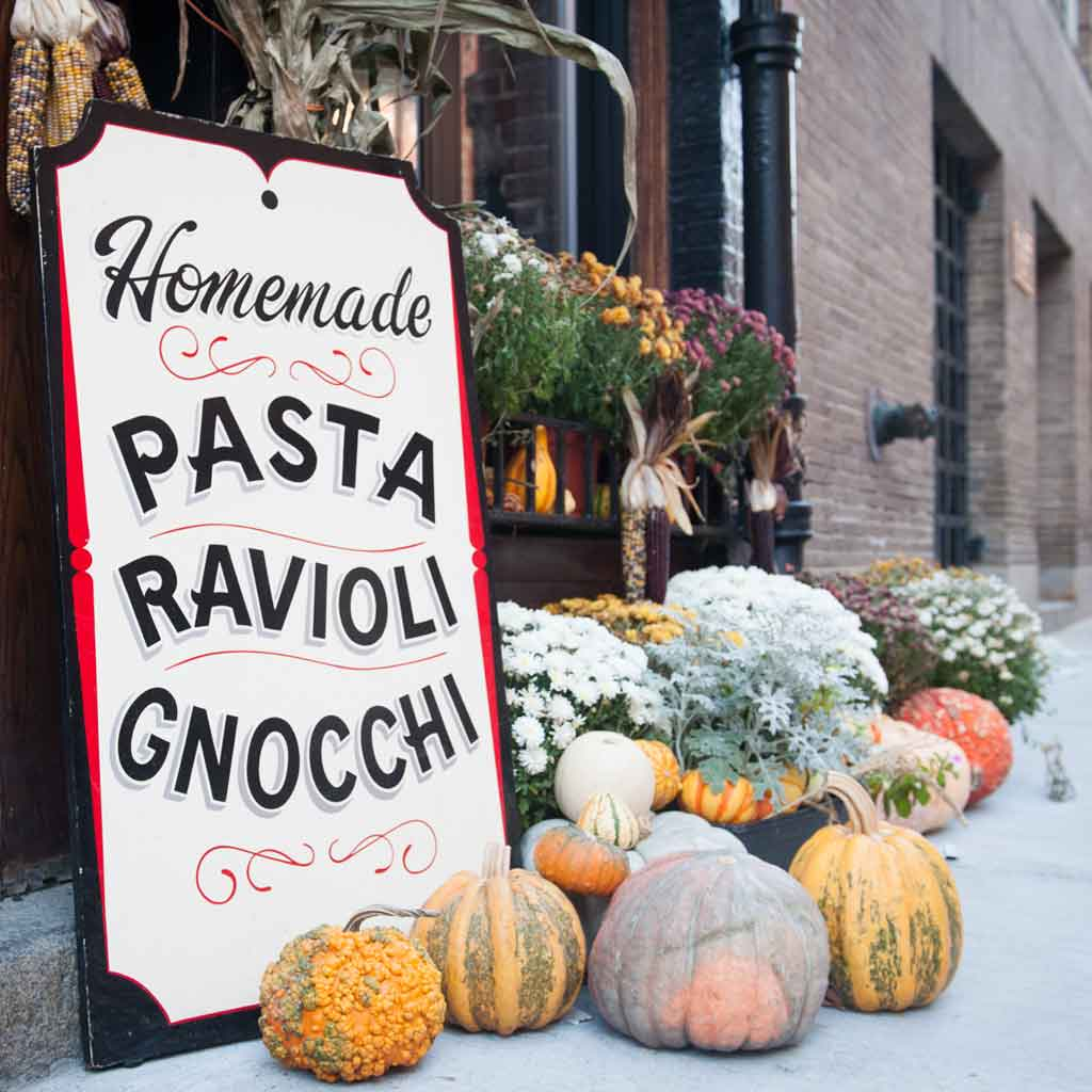 """Closeup of a sign that reads """"Homemade Pasta Ravioloi Gnocchi"""" with mums, gourds, and pumpkins surrounding it."""