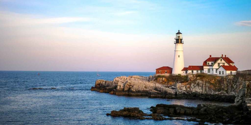 Landscape view of Portland Head Lighthouse on Cape Elizabeth in Portland, Maine with the ocean in the background.