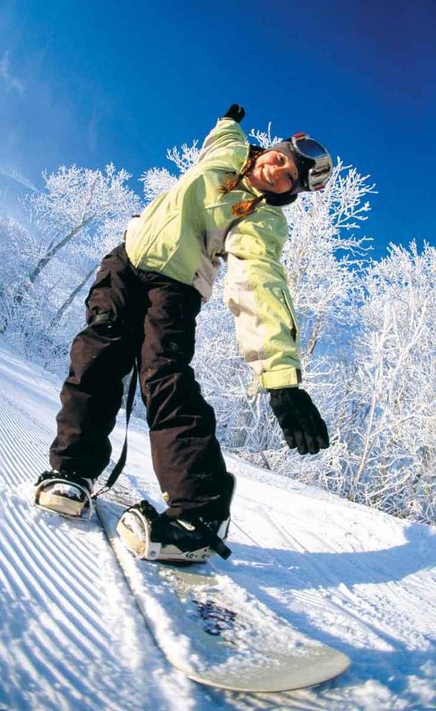 Woman snowboarding down Wachusett Mountain, wearing a light green coat and black ski pants.