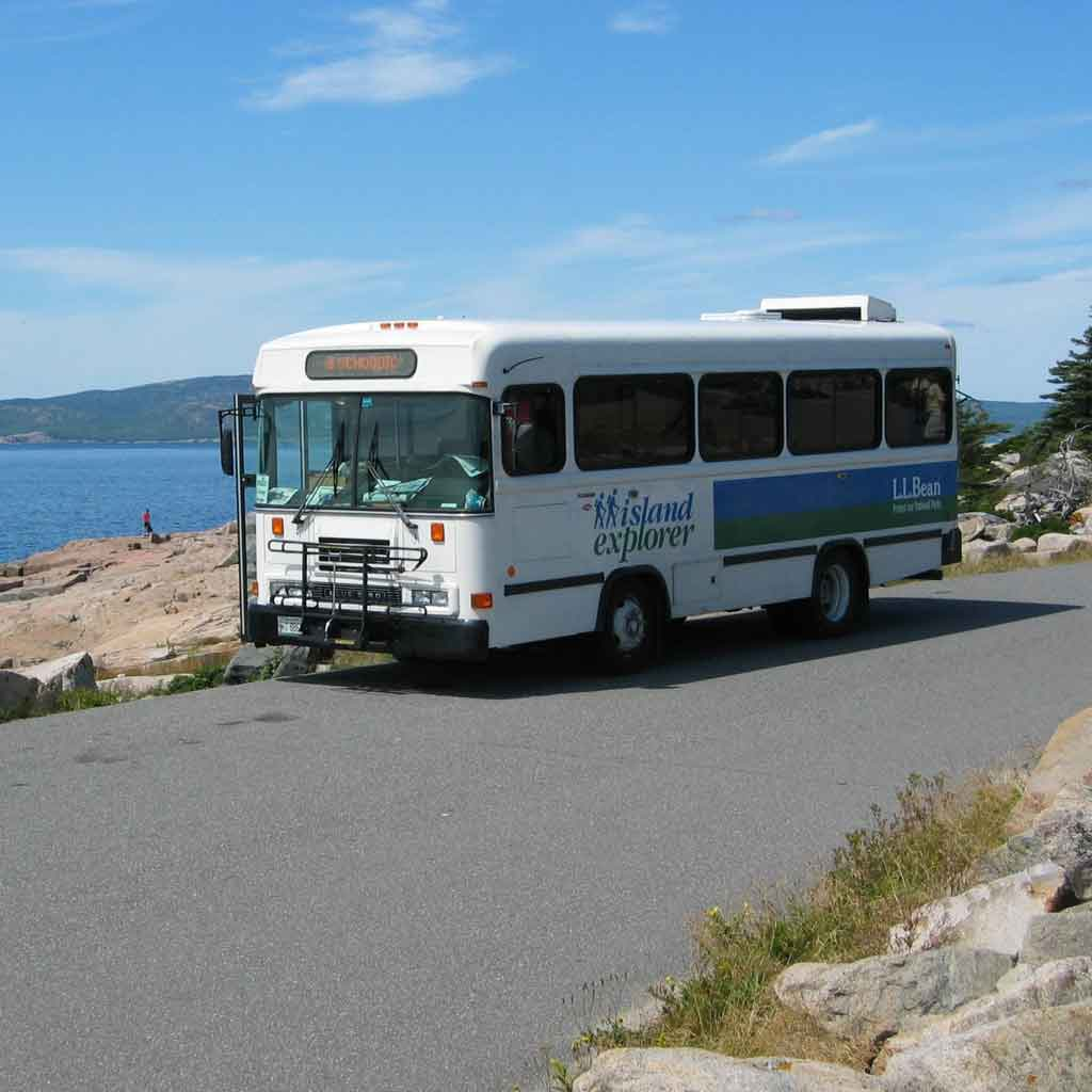 """Photo of a bus pulled over on the side of a road. Writing on the bus reads """"Island Explorer."""""""