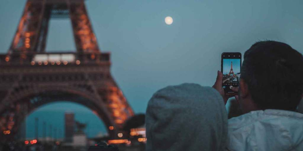 Photo of a man taking a photo of the Eiffel Tower with a smartphone camera.