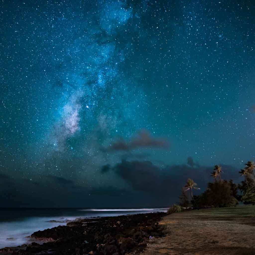 Navy blue sky with millions of stars, as seen from the shores of a tropical beach.