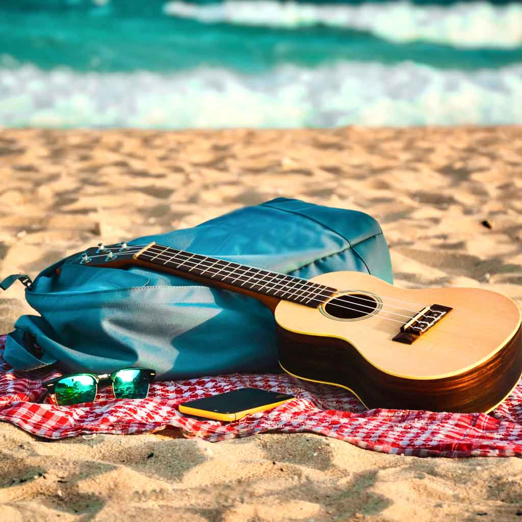 Closeup of a beach blanket on sand with a blue backpack, sunglasses, a guitar, and a smartphone.