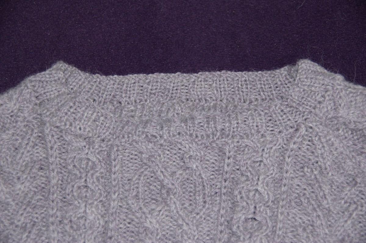 L'encolure tricotée séparément et cousue au point de mailles.
