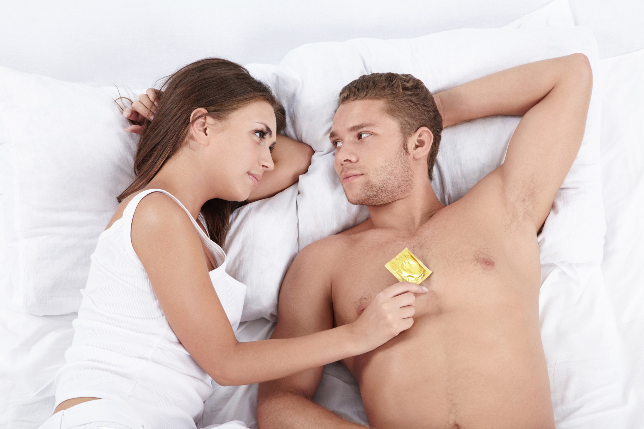 man and woman in bed with condom