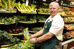 Fresh crops in grocery store with worker