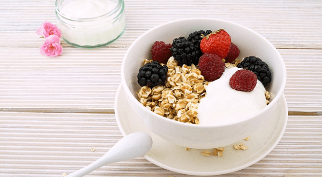 Whole grain oats topped with fresh berries and a dollop of yogurt close up.