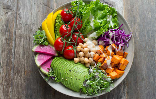 A bowl of fresh greens and fruits flat lay