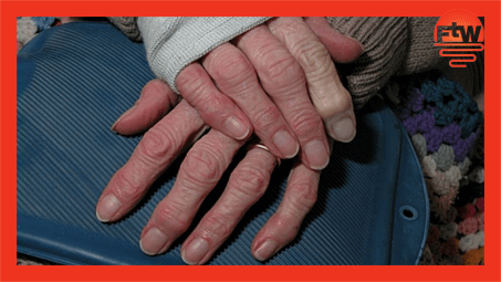 Elderly hands with a heated water bottle