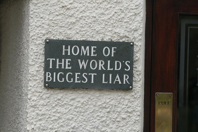 """Sign that says """"Home of the World's Biggest Liar."""""""