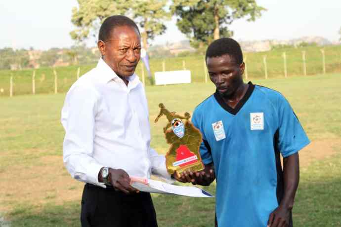 Viane Ssekajugo of Buganda recieves Man of the Match accolade and and envelope with cash from singer Jose Chameleon's father Gerald Mayanja