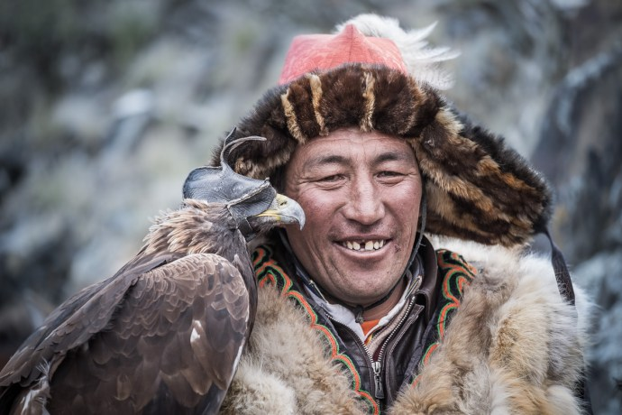 Kazakh eagle hunters are proud and majestic people. It has been a great privilege to photograph them. Eagle is wearing a cap on it's head to keep him calm and free from all distraction. It is removed just before releasing him to fly and catch the prey.