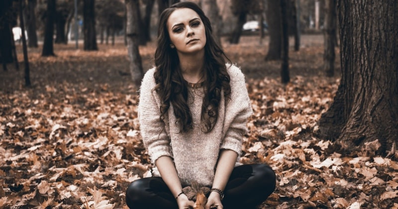 Emotional intelligence during parenthood with a sad woman sitting on leaves in the woods