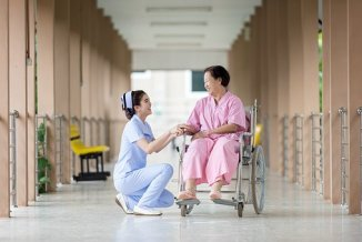 Nurse taking talking to wheel chaired lady