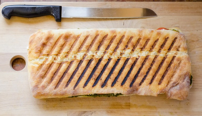 vegan pesto panini on cutting board, ready to serve