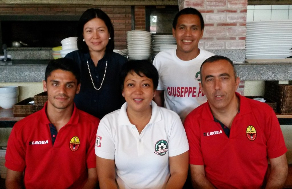 """Giuseppe Football Club owners Mylene Suarez (standing, left) and Rachel Genco (sitting, center) pose with Italian coaches Marco Cumbo (sitting, left) and Nicolo Ferrante (sitting, right). They are joined by GFC coach Oliver """"Bingbing"""" Colina (standing, right)."""