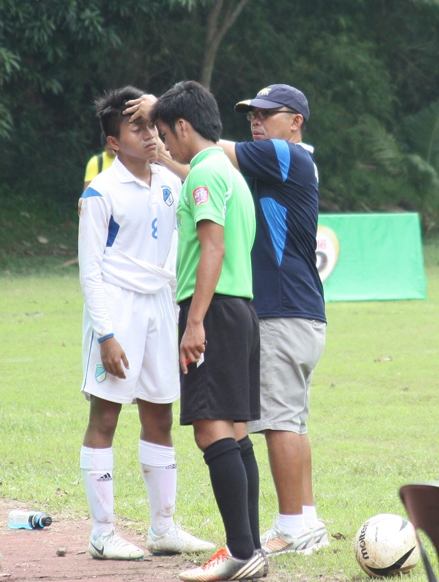 Team Visayas secondary football (Paref Springdale) coach Mario Ceniza checks the gash on his player's forehead during their match against NCR. The match ended in a draw but NCR took the title by virtue of a one-point goal difference.