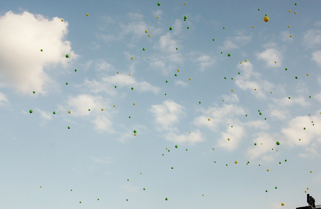 Students of the Apas National High School release green and yellow balloons into the air during their playground demonstration.
