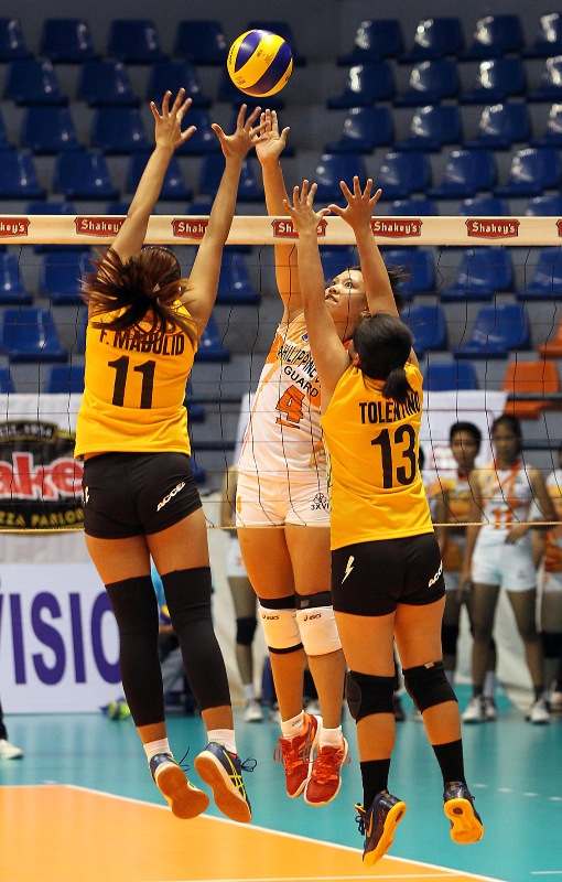 Coast Guard top hitter Rossan Fajardo goes for a power tip against Baguio's Florence Mae Madulid and Clarissa Tolentino during their Shakey's V-League Open Conference clash at The Arena.