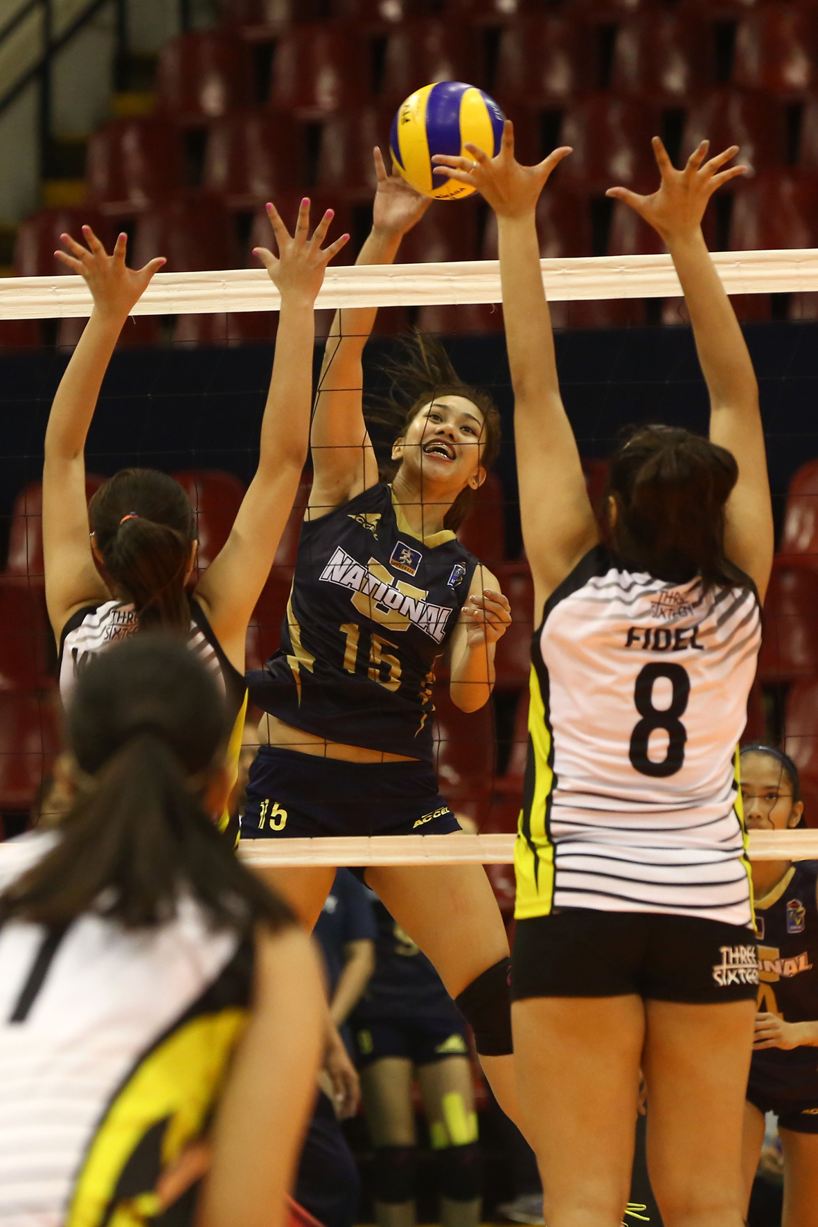 National U's Audrey Paran hammers in a kill against TIP's blockers, led by Rochelle Fidel (8) during their Shakey's V-League Collegiate Conference duel at the Philsports Arena.