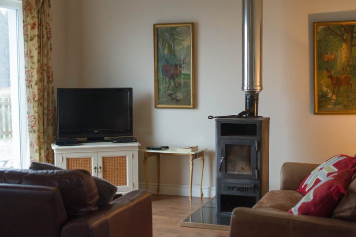 Photo of Poppies Cottage, Mull. Showing a wood burner and sofas