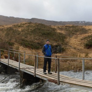Photo of a man standing on a small wooden footbridge over a small fast flowing river.
