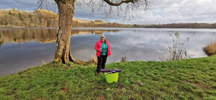 Photo of a woman stood at the side of a loch. Wearing lots of layers after swimming in cold water